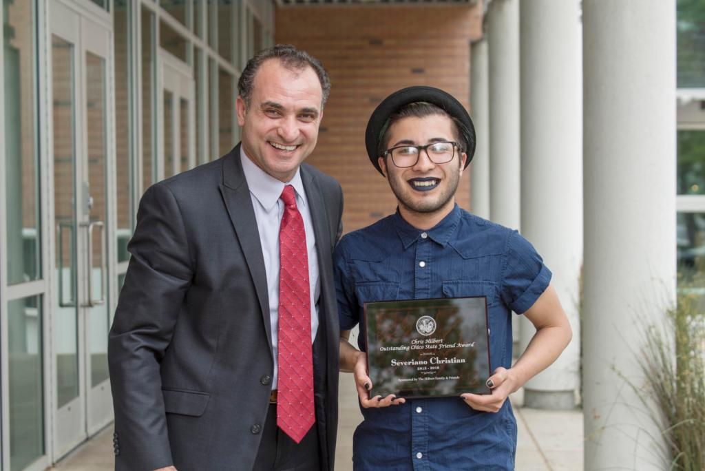 Ahmad Boura (left) presents Severiano Christian (right) with the Chris Hilbert Chico State Friend Award as students are honored at the 27th Annual University Awards Reception as part of Founders Week on Tuesday, April 12, 2016 in Chico, Calif. (Jason Halley/University Photographer)