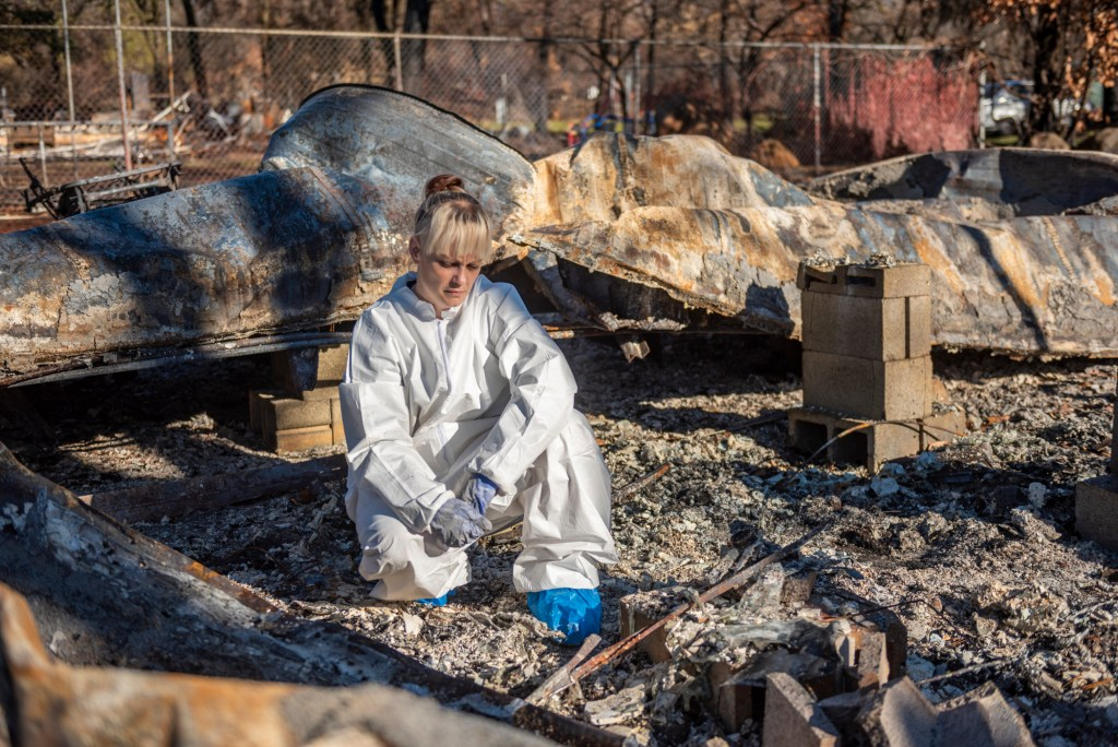 Wearing a protective suit for searching through rubble, Sabrina Hanes crouches in the ashes of the mobile home she was renting and braces herself not to cry.