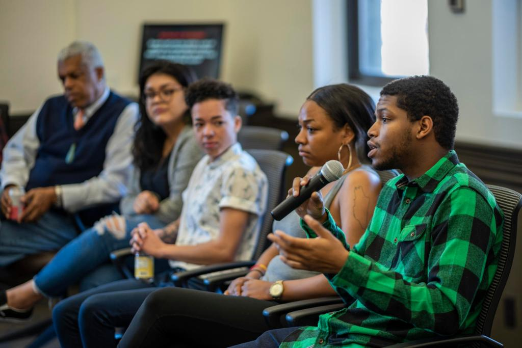 Kimani Davis II speaks into a microphone to a panel about diversity.