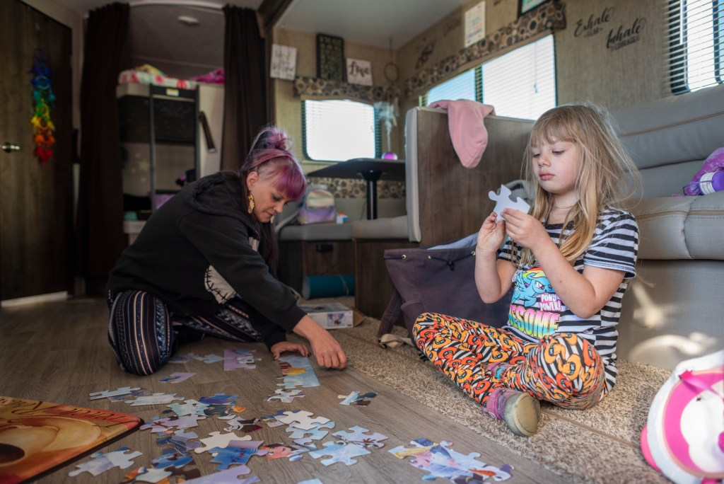 Sabrina Hanes and her 5-year-old daughter, Aroara, work together to assemble a children's puzzle on the floor of the trailer they are living in after the Camp Fire.