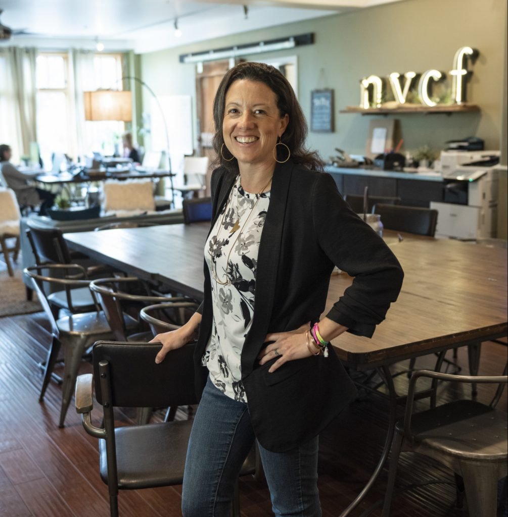 Alexa Benson-Valavanis stands in front of the conference table in the North Valley Community Foundation office.
