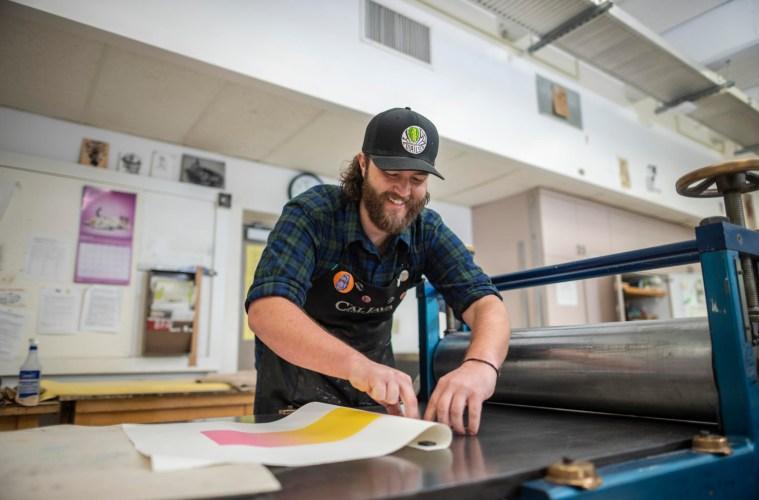 Brett Day works on the print making press.