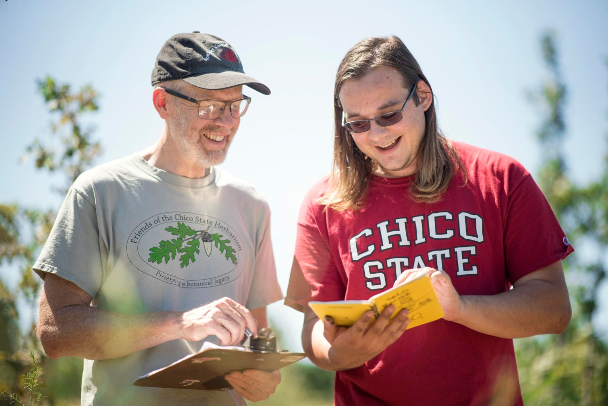 Chris Ivey stands with a clipboard and looks over at notes He-Lo Ramirez has written in his yellow field notebook.