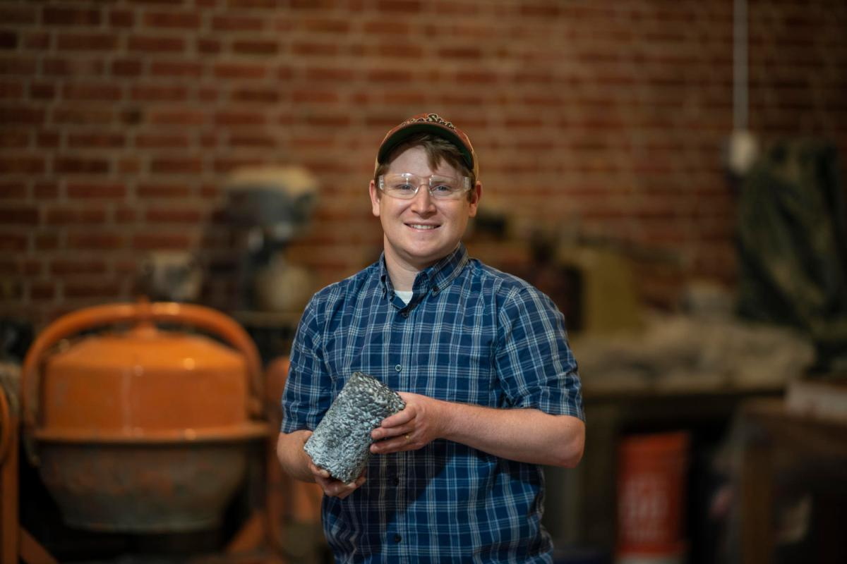 Portrait of Tim O'Shea holding a cylinder of concrete