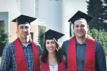 "Siblings Nick, Kayla, and AJ Gonzales wear their Chico State stoles as they stand in front of the boiler-chiller towers that say ""Chico State."""