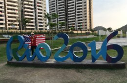 Kym Crosby waves the American Flag and stands behind the Rio 2016 Paralympic sign.