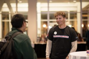 First-Year Experience Program Lecturer Nate Millard greets students as they arrive at Wildcats Vote! in October