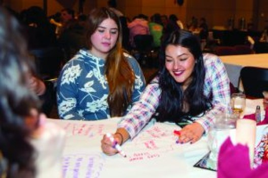 Students write during an exercise during a recent REACH program dinner.