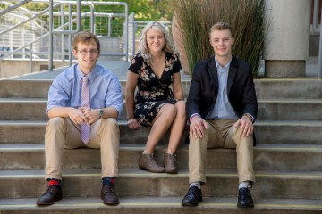 Blake Northam, Camille Davis, and Aaron Bursten sit on the stairs of the BMU.