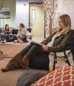 Woman studies a book while sat in on a bean bag chair. Twinkle lights illuminate the room.