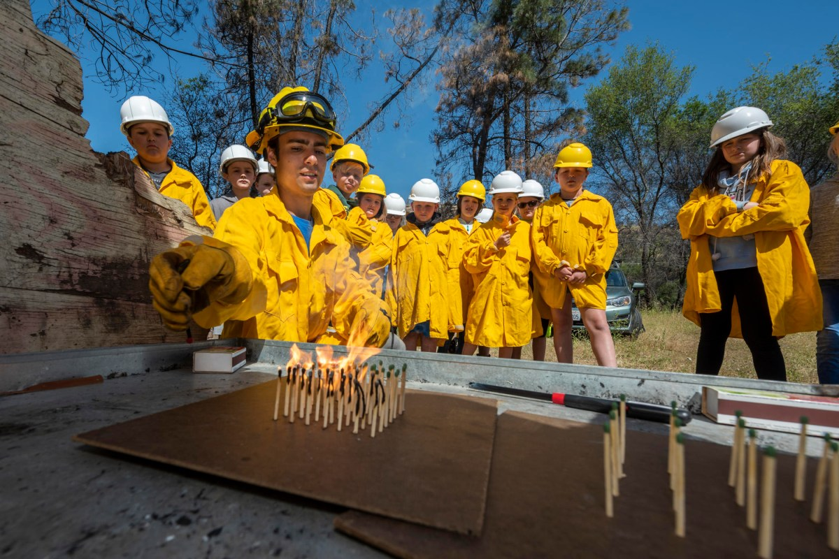 A firefighter lights a grove of matches standing upright on a flat surface as fourth graders watch behind him in protective yellow clothes.