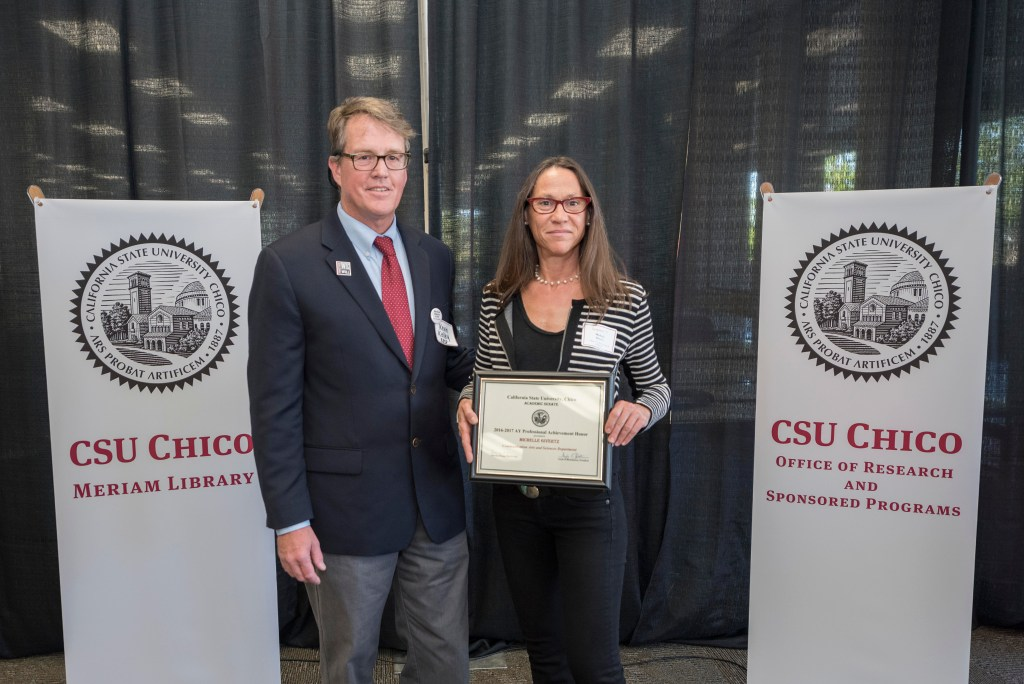 Michelle Givertz, a professor in the Department of Communications Arts & Sciences, holding her Professional Achievement Honors award and stands next to Kevin Kelley, interim associate vice president of the Office of Research and Sponsored Programs.