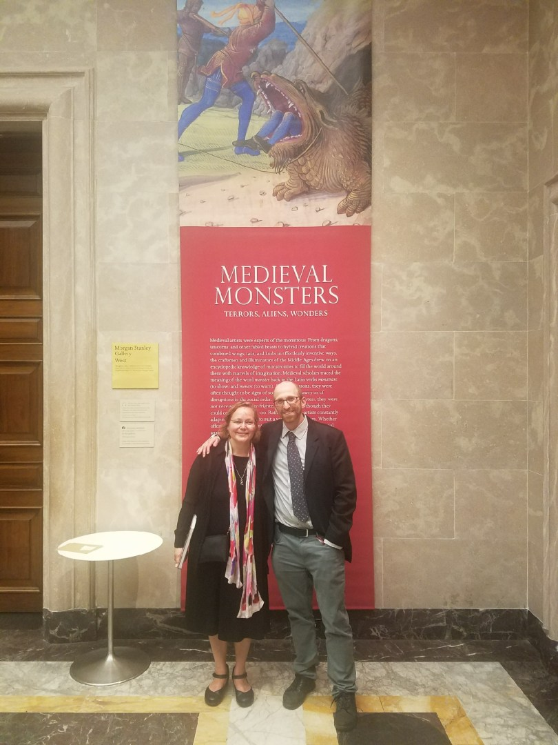 Sherry Lindquist and Asa Mittman pose in front of a promotional banner for their exhibit at The Morgan.