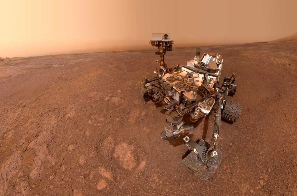 The Curiosity Mars rover sits on the dusty red surface of Mars.