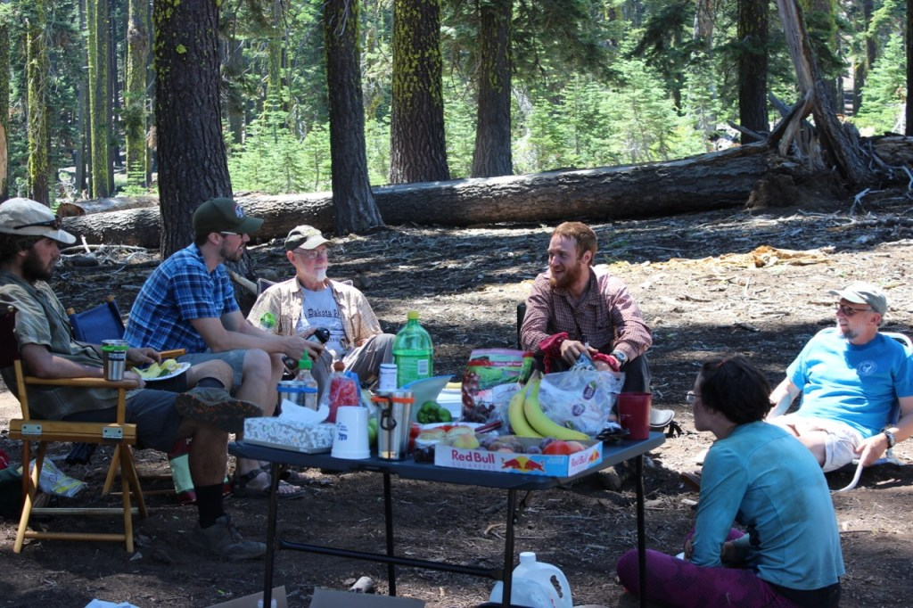 A group of hikers sit around a table of refreshments.