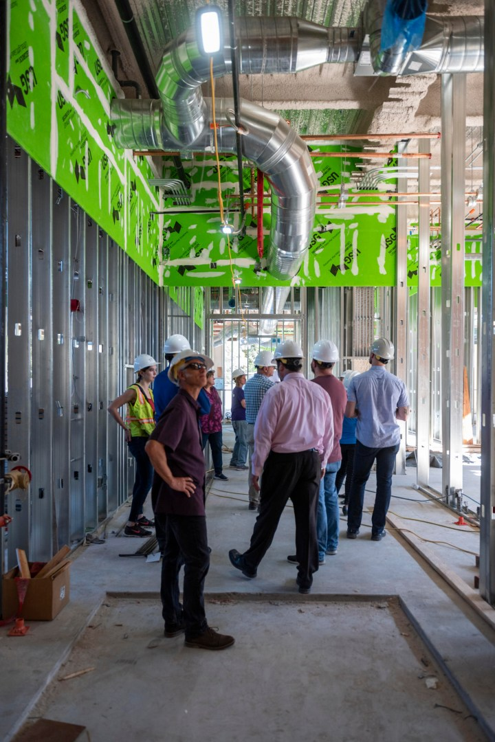 A group of people in hardhats stands in the hallway of the new building, which has construction materials scattered about.