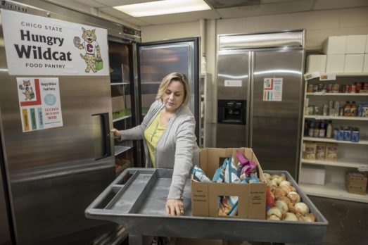 Moroney places onions in a refrigerator at the Hungry Wildcat Food Pantry