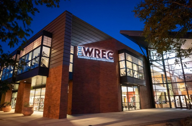 The WREC sign is illuminated at night, with views of the workout equipment visible through the windows.