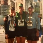 Vanden Bosch stands with two friends in running clothes and finishers medals
