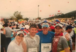 Group of four runners wearing race bibs