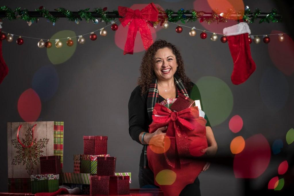 Portrait of Lisa Saldano holding holiday gifts.