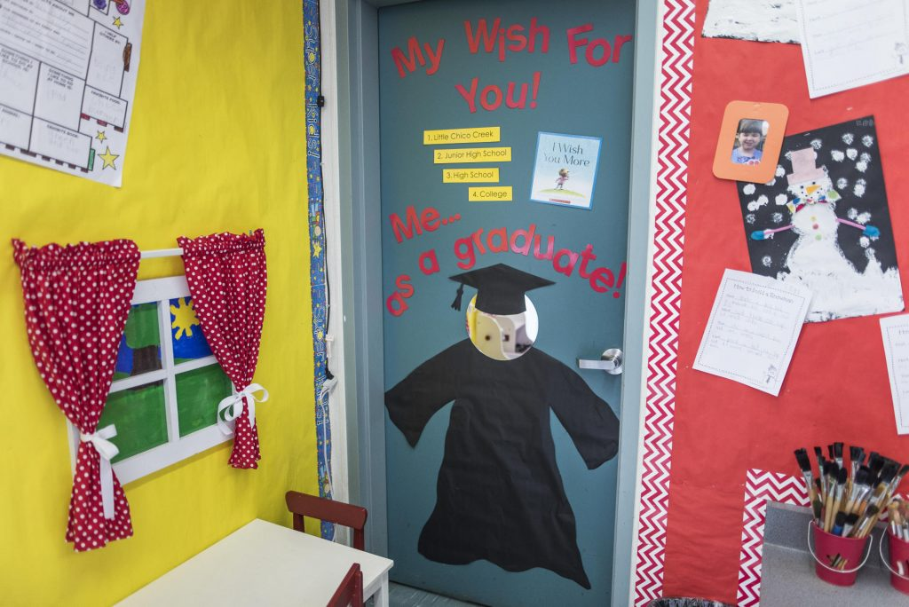 "Corner of the classroom decorated with a graduation cap and gown with a sign that reads ""Me as a graduate!"""