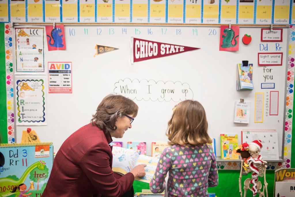 Hutchinson looks at a book with a young student. In the background a Chico State pennant hangs on the whiteboard