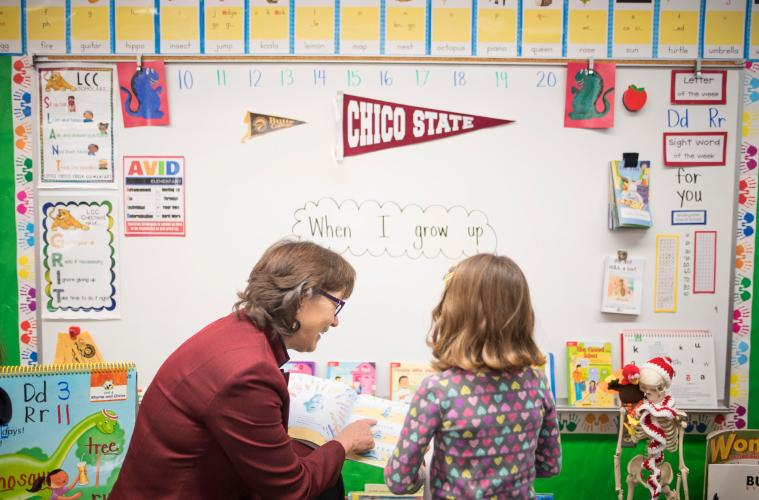 President Hutchinson looks at a book with a kindergarten student
