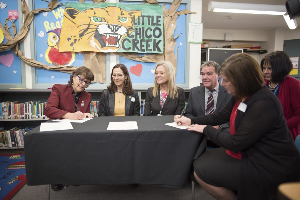 Four educators sit at a table in front of a Little Chico Creek sign, with President Gayle E. Hutchinson signing the Butte County Promise.