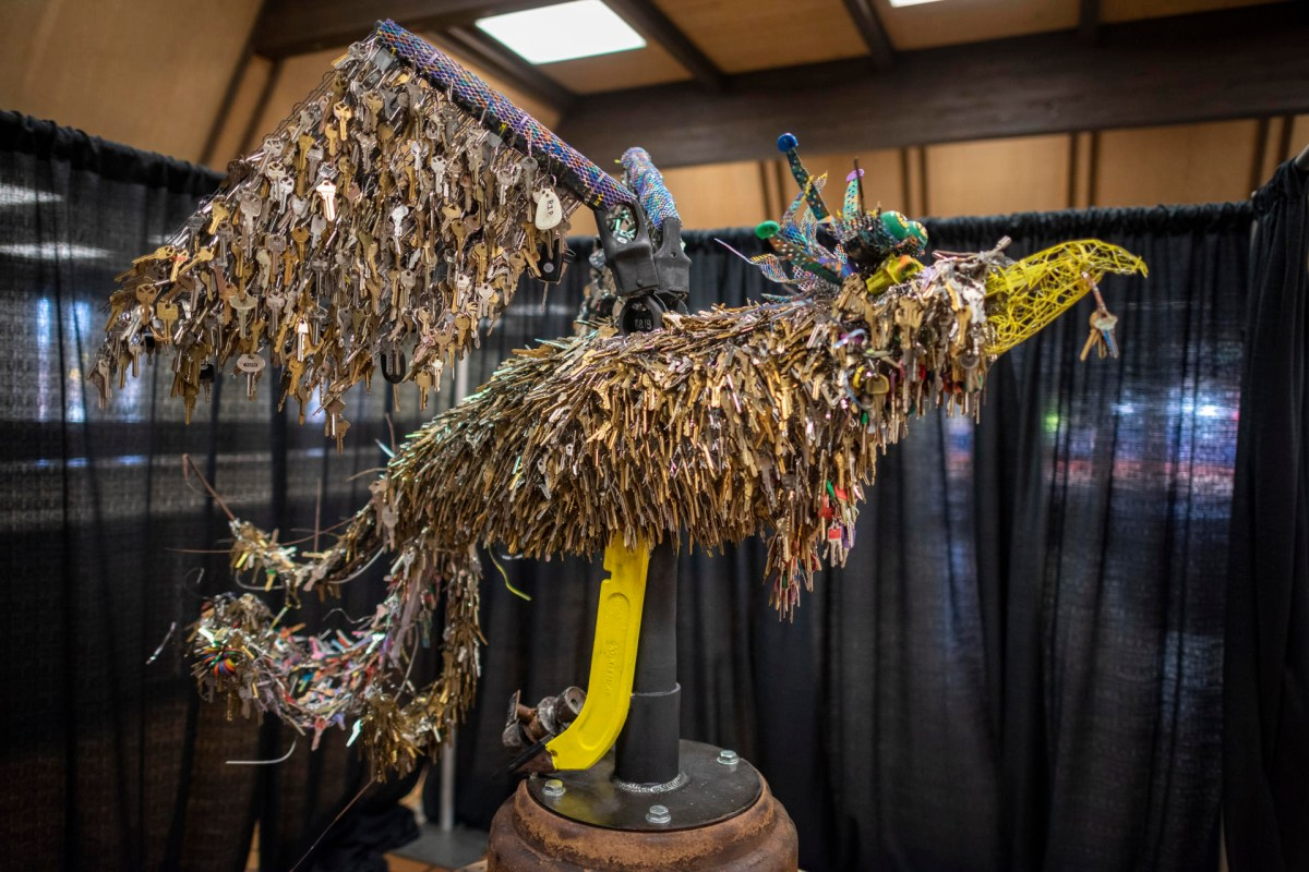 An art piece featuring thousands of keys in the shape of a bird is displayed in front of a black curtain.