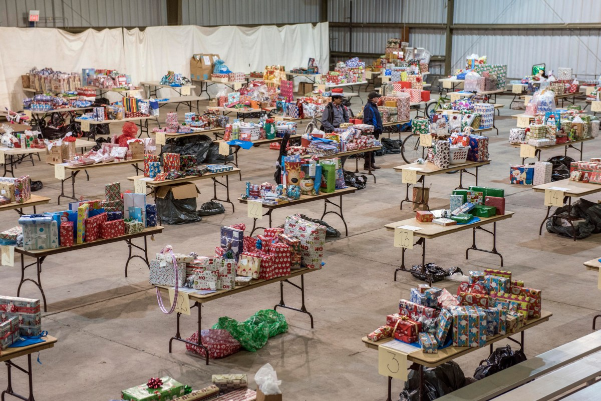 The University Farm Pavilion is filled with folding tables covered in wrapped holiday gifts.