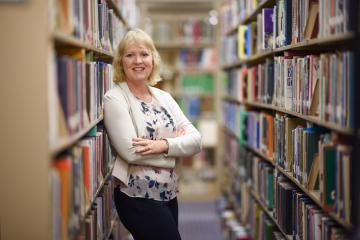 Corina Yetter leans against a shelf of books in the Meriam Library.