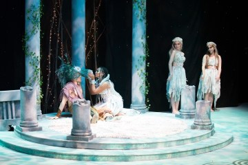Actresses in long white dresses rehearse on an elaborate set design.
