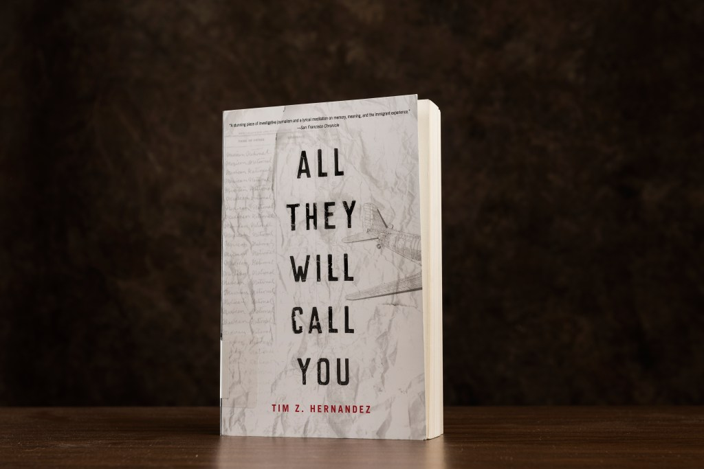 "The book ""All They Will Call You,"" with a white cover, is silhouetted against a black background"