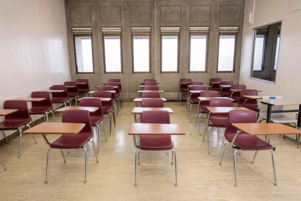 Rows of desks are lined up inside a classroom.