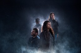 Four students, two male and two female, stand in partial silhouette and smoky light.