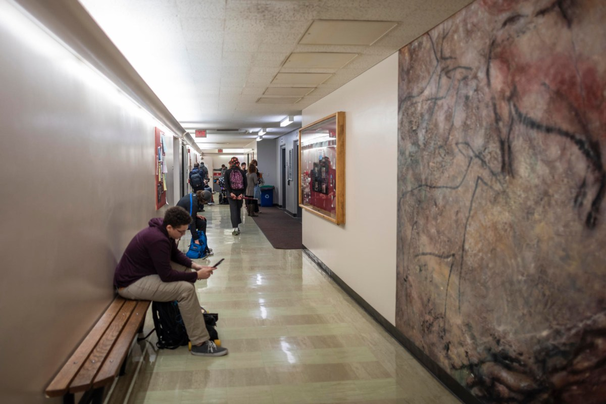 Students sit in the hallway of Butte Hall while waiting for class to start.
