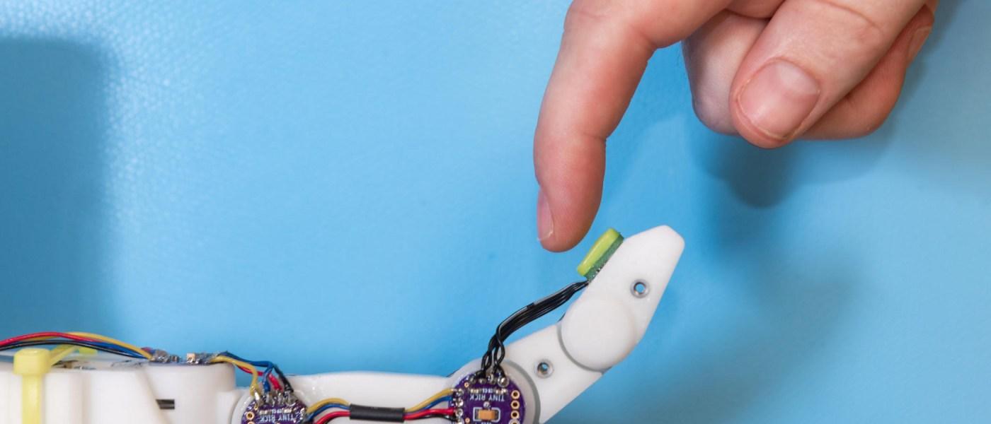 A human finger touches a finger sensor on a mechanical finger.
