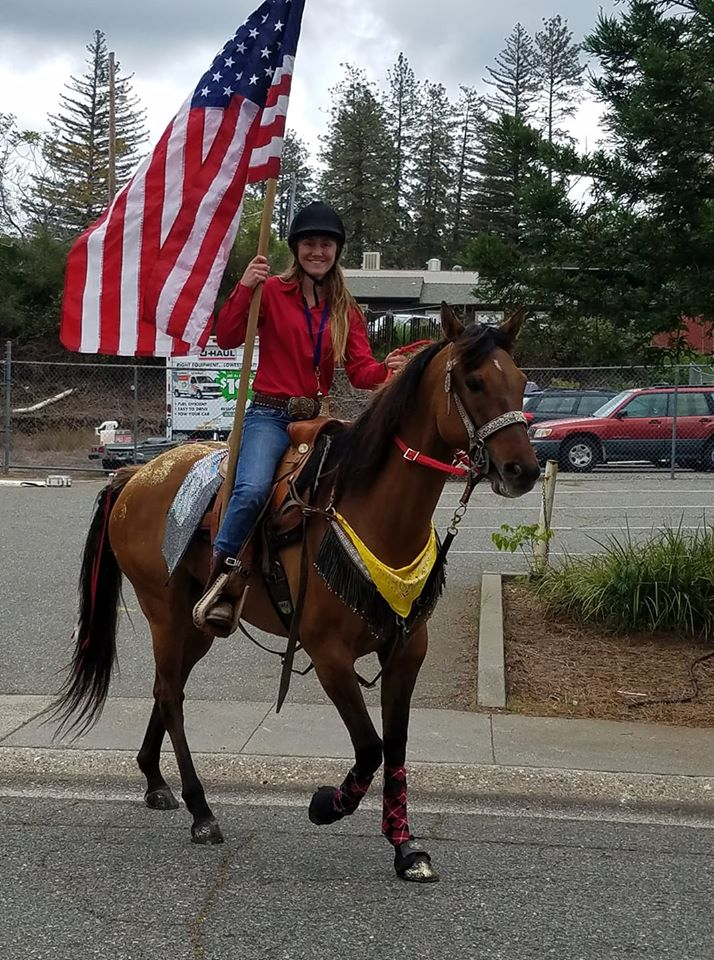 Cassidy Sabral holds a large American flag while sitting on the back of a horse.