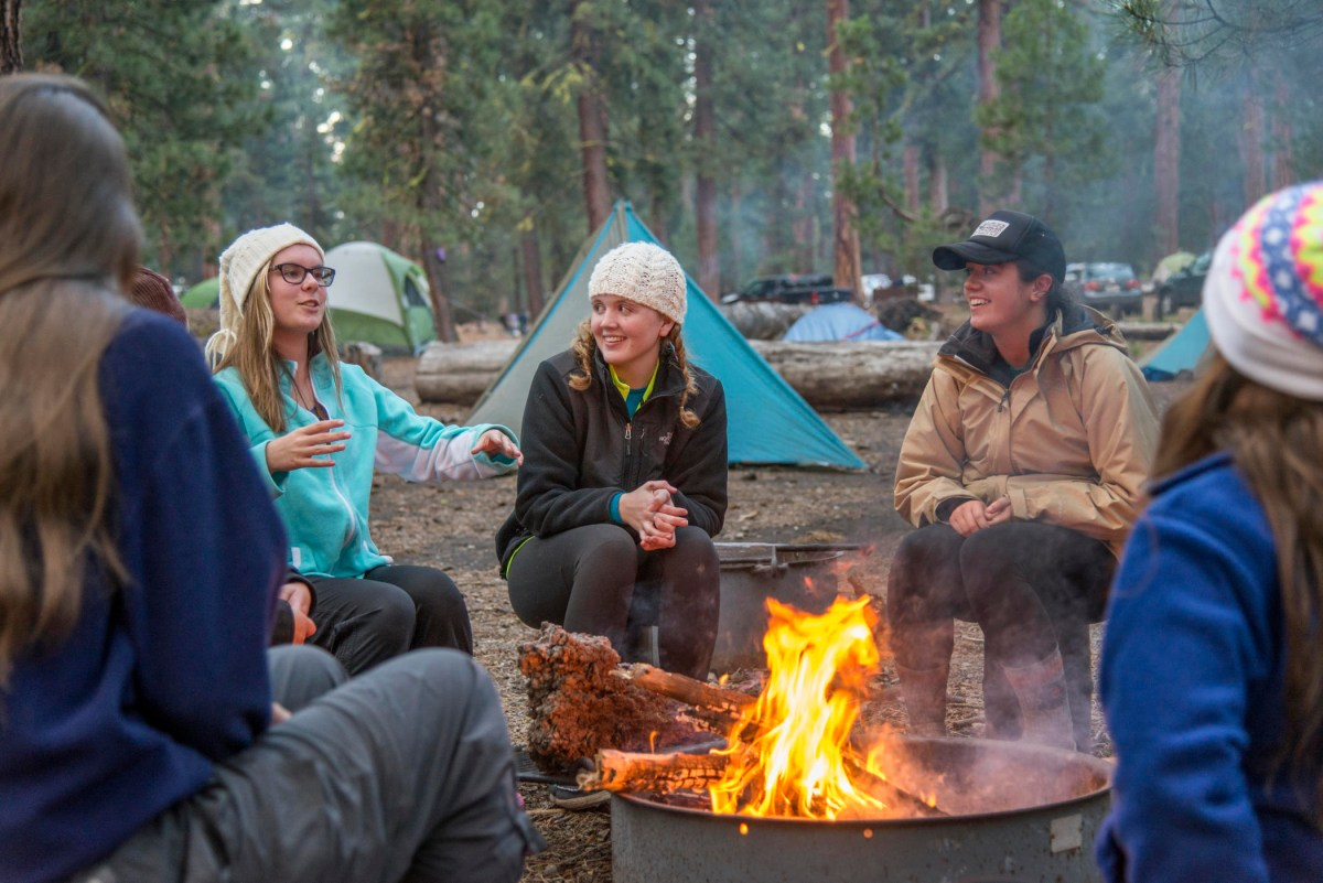 Students tell stories and laugh around a camp fire, with their tents behind them.