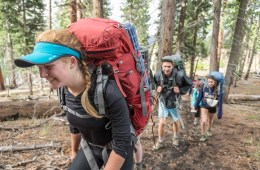 A student hikes hunched over with a heavy backpacking pack on her back as other students follow behind in a forest.