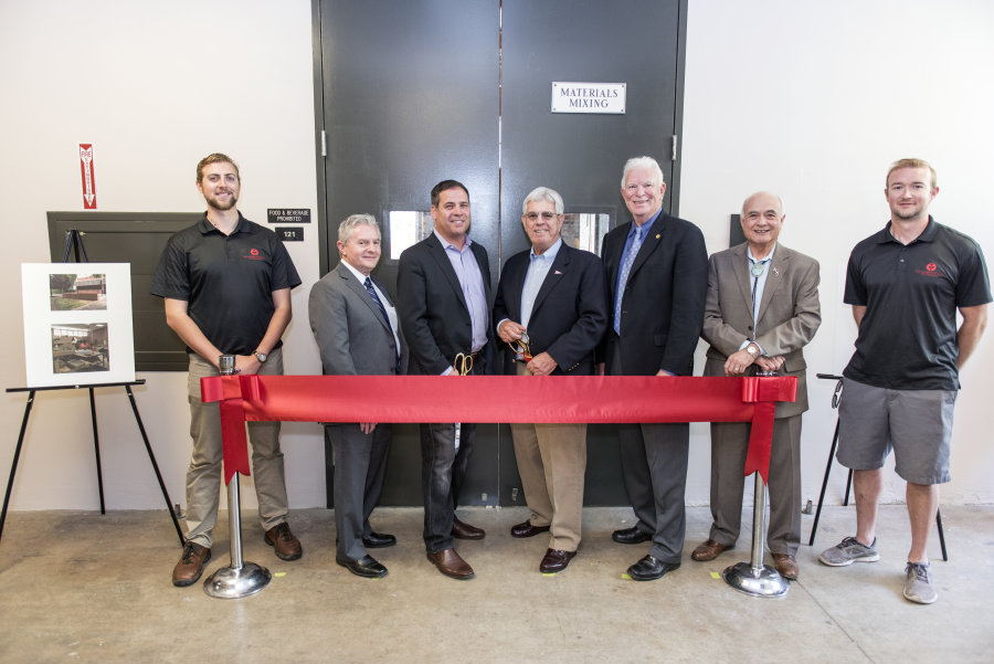 Murphy and other patrons stand at a ribbon-cutting for the concrete lab.