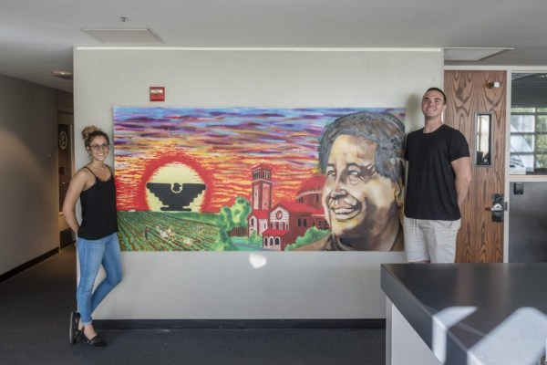 Two students stand on either side of a mural of Cesar Chavez. The mural shows a sunset, a black eagle logo, Chico State buildings and a field.