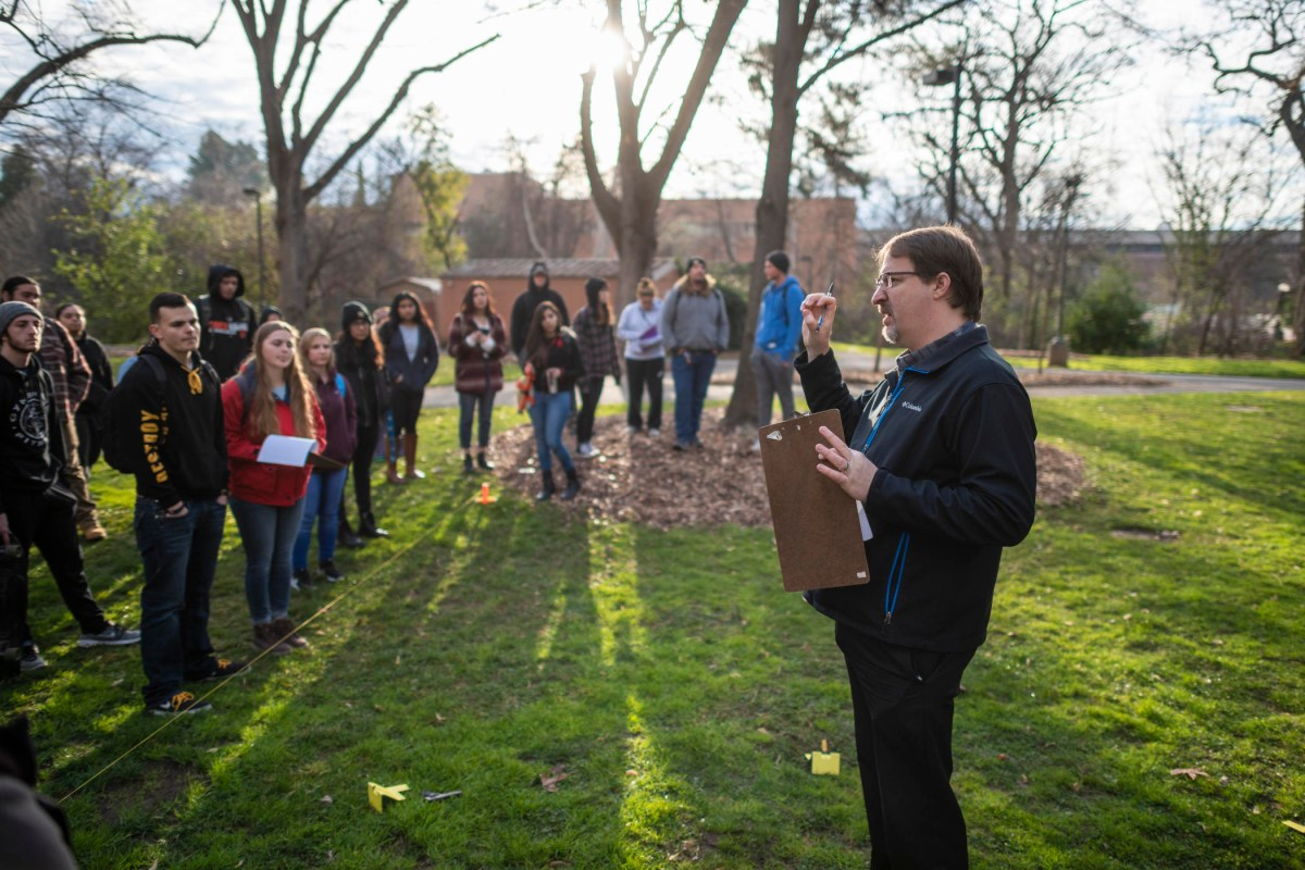 Eric Bartelink speaks to a group of forensic anthropology students at a mock crime scene on the Butte Hall lawn.