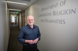 Bruce poses in the hallway of the Department of Comparative Religion and Humanities.