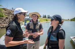 President Gayle Hutchinson laughs with graduate students Valerie Sgheiza and Mallory Peters as they stand on a dock on the Sacramento River.