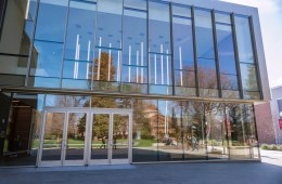 Kendall Hall is reflected in the front windows of the Arts and Humanities building on a winter morning.