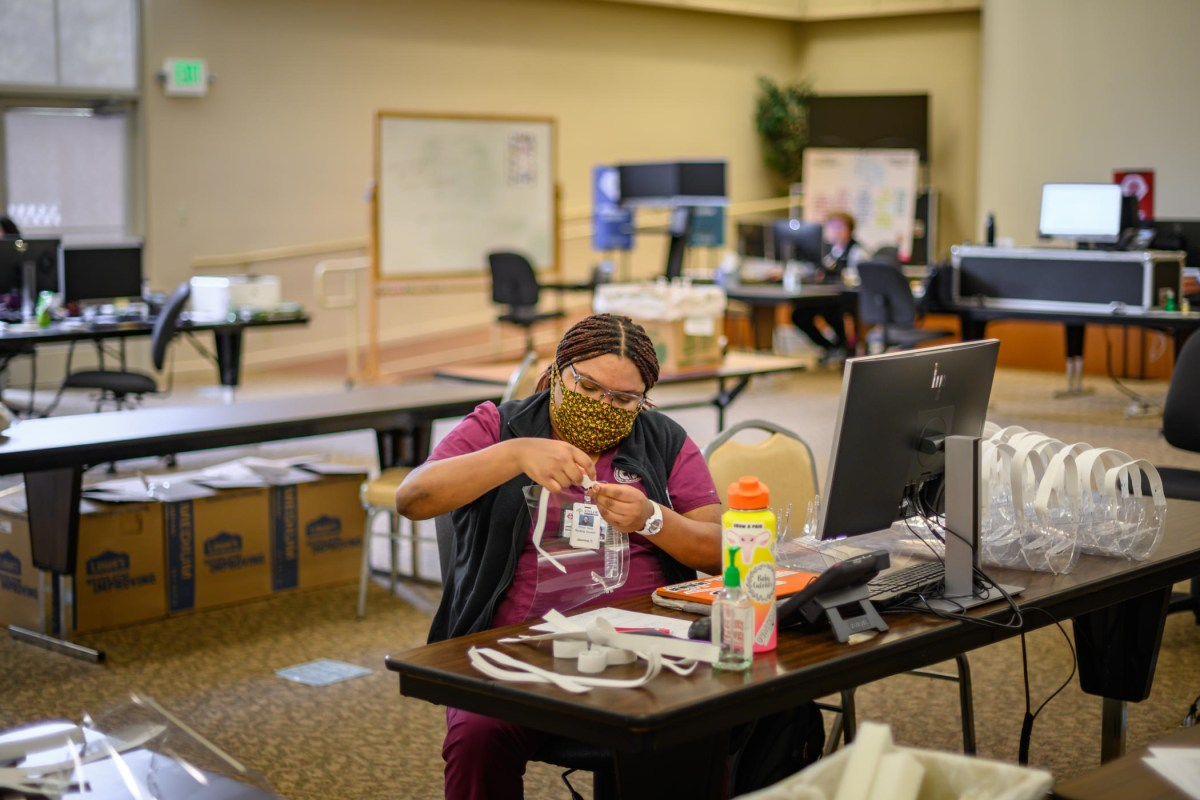Jasmine Taylor assembles face shields at a desk.