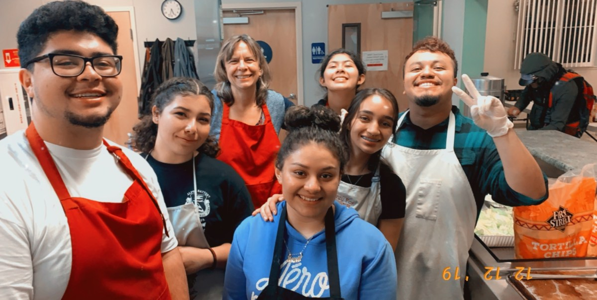 Enrique Galvan and a group of students pose for a picture at a homeless shelter after working in the kitchen.