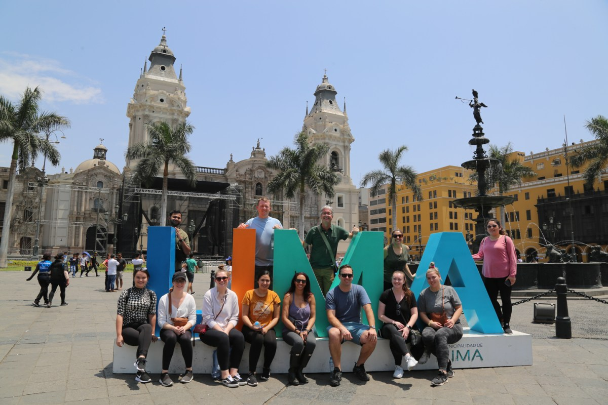 "Students pose with cut-out letters that spell ""LIMA"""